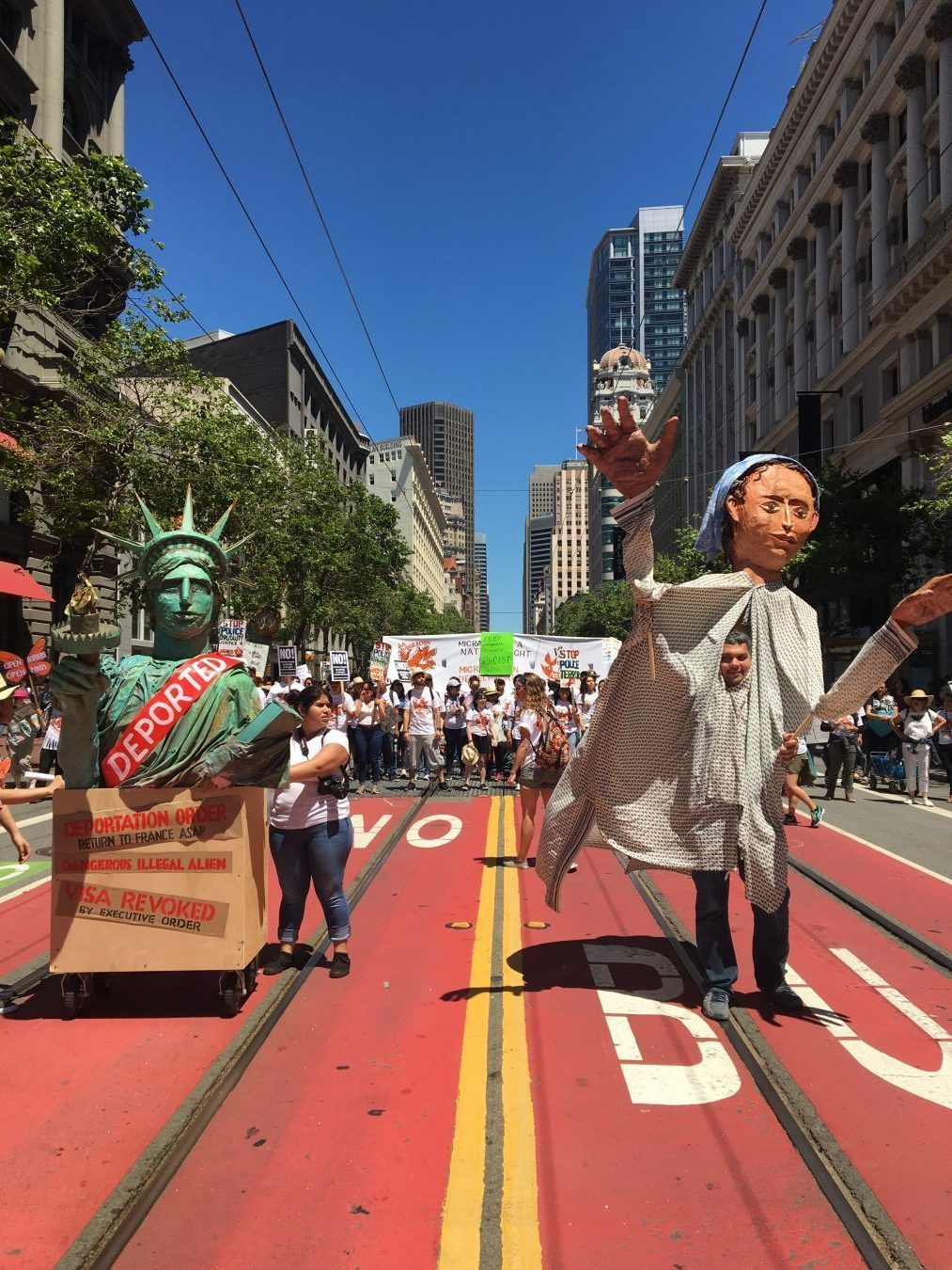 Marchers carried a large figures representing liberty and immigrants up Market Street in San Francisco.