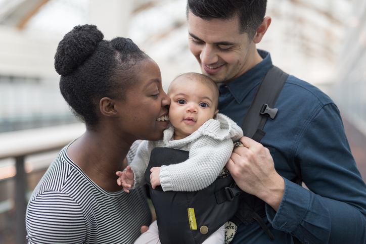 Affectionate multi-ethnic couple are shopping with their baby daughter who is riding in a baby carrier