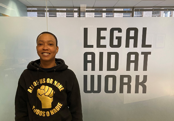 Image of Katie Dixon in front of Legal Aid at Work Logo