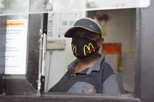 Picture of fast food worker in a drive-through window wearing a face mask