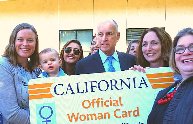 "Picture of advocates for paid family leave standing with Governor Brown before an enlarged California license that says ""Official Woman Card"""