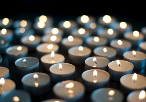 Image of lit candles in a dark room