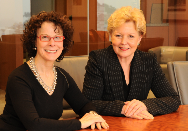 Image of Mary Jo Shartis sitting at a wood table with Legal Aid at Work President Joan Graff