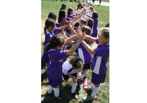 Image of young girls high-fiving each other after soccer game